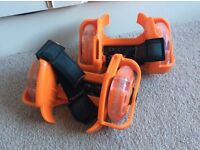 Pair of orange light up clip on roller skates.