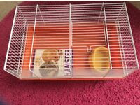 Hamster cage With book and dish .