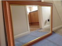 Large wooden mirror with gold trim.