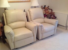 Two cream leather electric reclining chairs.