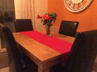 Light oak dining table with 4 brown high back faux leather chairs