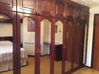 Fitted bedroom furniture with solid wood and smoked glass doors