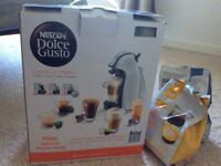 Nescafé dolce gusto coffee machine and two bags of coffee pods