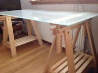 Glass topped desk with trestle supports. IKEA glass desk top on adjustable trestles.