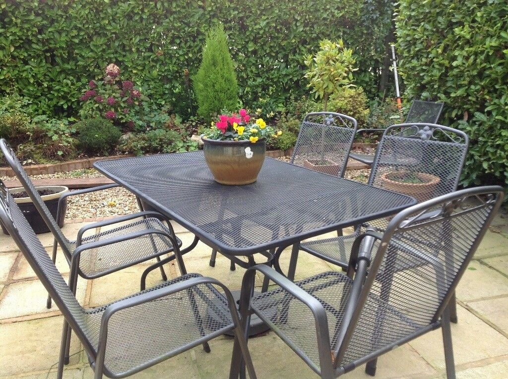 Garden dining table and six carver chairs with matching cushions.