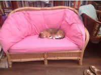 Wicker two seater settee, pink cushions, clean condition