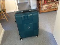 Hard shell suitcase. Four wheels. New but has been marked by couple of paint splotches.