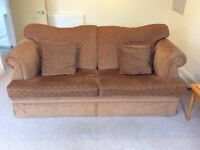 3 piece suite in burnt orange / brown colour. 3 seater sofa and 2 arm chairs with matching cushions