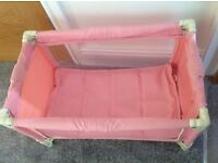 Dolls travel cot in pink.