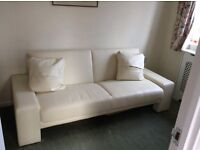 Cream faux leather three seater sofa folds flat to single bed.