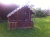 Children's wooden playhouse with loft and veranda