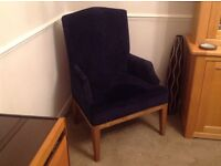 Navy blue armchair with wooden legs.