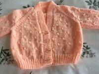 HAND KNITTED BABY CARDIGAN. PEACH. NEW.