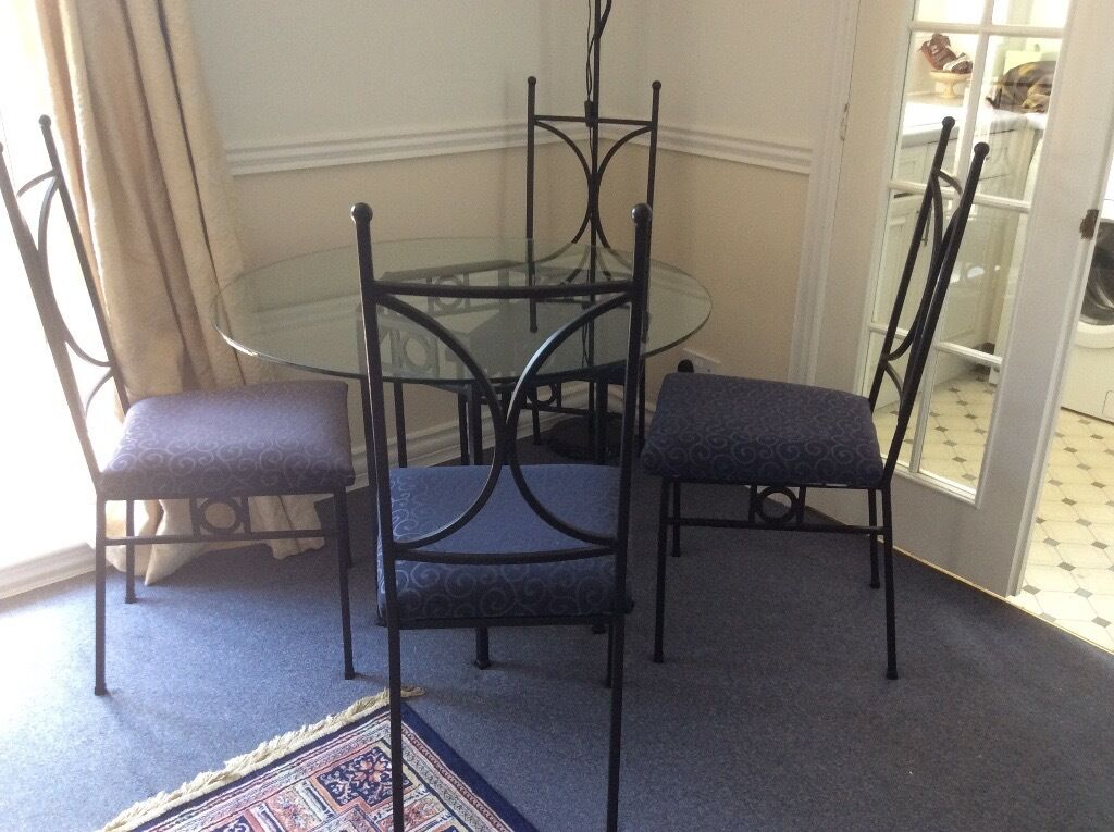 Glass top table and chairsin Southampton, HampshireGumtree - Glass top table with four chairs. Strong wrought iron base and chair frames. Table top 100 cms dia. Dark blue seats. Collection only