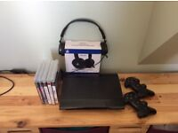 PS3 slim console plus 2 dual shock controllers boxed headset and games