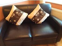 Small faux leather two seater sofa, slightly sun damaged, hence realistic price