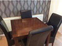 Extending Mahogany dining table and four brown chairs