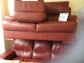 Red leather 3 and 2 seater sofas with matching pouffe