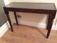 Carved wood console table with glass top