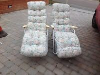 Two padded garden recliner seats, cream base, floral covers. Very comfortable.