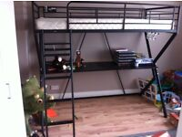 Black single bunk bed with desk space.