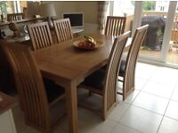 Solid oak dining table and 6 leather upholstered chairs.