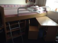Bunk bed with shelving and pull out desk and chair.