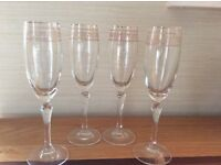 4 champagne glasses with gold patterned trim