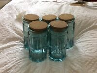 5 storage jars with cork lids.