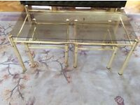 Metal and glass coffee table with two side tables that nest underneath.