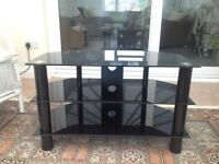 "TV stand with black glass and legs, for TV up to 40"" screen, three shelves, cable management holes."