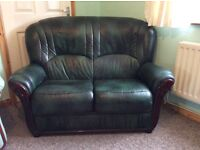 GREEN LEATHER 2 SEATER SOFA WITH HAND CARVED WOOD TRIM IN EXCELLENT CONDITION