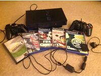 PlayStation 2 with controllers and games.