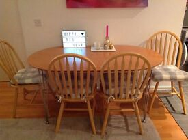 wooden dining table with 4 chairs with blue & white cushions