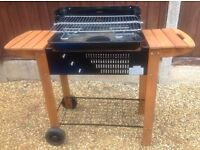 "Charcoal BBQ ""trolley style"" with wheels; wooden side shelves & metal rack underneath"