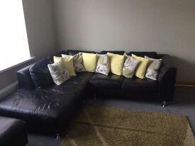 Black leather sofa and footstool
