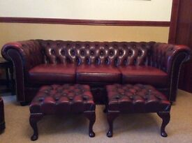 Classic chesterfield sofa with two matching ambassador chairs and footstools, all blood red
