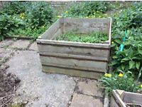 Five assembled wooden raised beds with copper bands