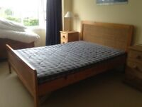 Wooden framed double bed with wicker head and foot board inlay.