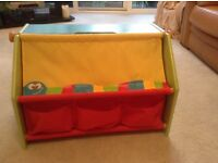 Child's toy box with front pouches and drop down cover to hide toys when not in use.