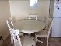 White round table sits 4 when extended sits 6 with 4 chairs.
