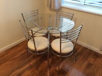 Glass dining table and four chairs, new condition.