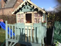 Childrens wooden playhouse with green slide