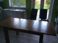 Solid oak unmarked extendable dining table and 4 chairs.