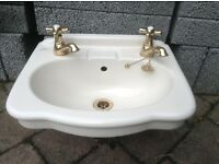 Ideal Standard cream ceramic cloakroom wash basin with taps.