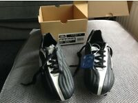 Football boots boxed and unused.