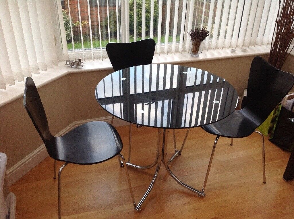 Smoked glass dinning table with 3 chairs.
