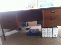 A large sturdy desk in good condition except that the top surface is very scratched.