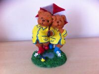 Cute little ornament of two teddies with yellow coats holding an umbrella