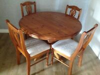 Antique pine extendable table with four chairs.